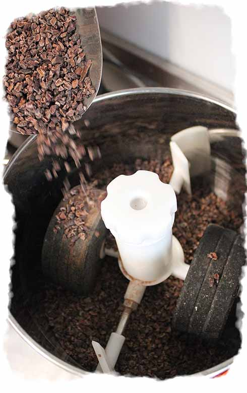 Pouring cacoa nibs into a grinder ready to be ground.