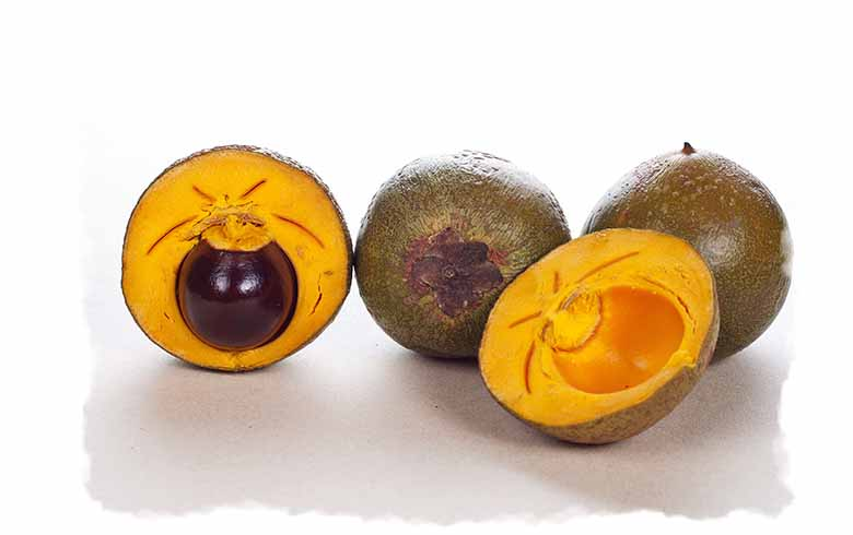 Three Lucuma fruit, one cut in half to show the sweet yellow inside.